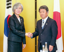 会談を前に握手する韓国の康京和外相(左)と茂木敏充外相=11月23日