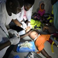マラリアの治療のため、ぐったりする子どもの頭に点滴用の針を刺す医師たち=ナイジェリア・ボルノ州マイドゥグリで2019年9月27日、山崎一輝撮影