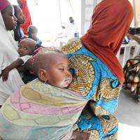 小児集中治療室で、受診を前に母親の背中で眠る患者の子ども=ナイジェリア・ボルノ州マイドゥグリで2019年9月30日、山崎一輝撮影