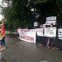 裁判所の決定後、「学生の声を消すな」「国は表現の自由を保障していない」などと書かれた横断幕を掲げて抗議する学生ら=国立北スマトラ大学周辺で、ヤエル・シナガさん提供