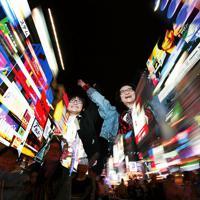 グリコの看板の前でポーズをする外国人観光客ら=大阪市中央区で2019年10月23日、山田尚弘撮影(午後9時18分から2分間に撮影した4枚を合成)