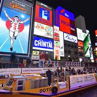 グリコの看板の前でスピードを落とす遊覧船。一番の撮影スポットだ=大阪市中央区で2019年11月27日、山田尚弘撮影