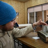 陶器で作った旧ソ連軍の戦車「KV-2」の説明をする息吹フレイルさん。奥は「戦艦大和」=滋賀県甲賀市信楽町の壺八窯で2019年11月30日午前11時38分、礒野健一撮影