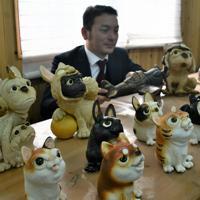 小賀大介さん(奥)が制作した「こま犬のかぶり物をしたフレンチブルドッグ」など、個性的な表情がかわいい犬の置物=滋賀県甲賀市信楽町の壺八窯で2019年11月30日午後0時10分、礒野健一撮影