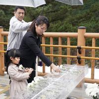 中央自動車道笹子トンネルの上り線出口付近の東京側にある慰霊碑に献花する遺族=山梨県大月市で2019年12月2日午前8時7分(代表撮影)