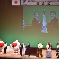 花角知事(中央左)から宮崎県の郡司行敏副知事に大会旗が引き継がれた=新潟市中央区の県民会館で