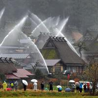 放水銃の点検で水柱が上がる「かやぶきの里」=京都府南丹市美山町北で2019年12月2日午後1時33分、平川義之撮影