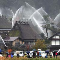 放水銃の点検で水柱が上がる「かやぶきの里」=京都府南丹市美山町で2019年12月2日午後1時37分、平川義之撮影