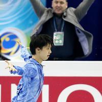 男子SPでジャンプを決めた羽生結弦(左)と拳を突き上げるコーチのブライアン・オーサー(奥)=マリンメッセ福岡で2013年12月5日、貝塚太一撮影