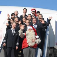 飛行機から降り、手を振るサンタクロースとフィンエアーの運航乗務員=成田空港で2019年12月3日午前10時35分、中村宰和撮影