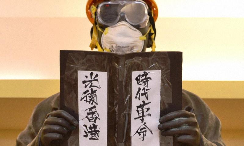 ヘルメットやゴーグル、マスクを付けられた孫文像。「時代革命」(革命の時だ)「光復香港」(香港を取り戻せ)のスローガンも張られていた=2019年11月29日、福岡静哉撮影