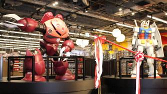 「成田アニメデッキ」内のグッズショップに飾られた「RX-78-2ガンダム」(右)と「シャア専用ズゴック」の立像。オープン前日の発表会でお披露目された=2019年11月27日