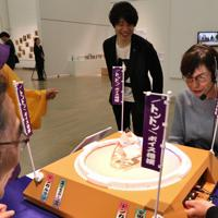 「ここから4」で「トントンボイス相撲」を楽しむ人たち。開発した大瀧篤さんが笑顔で見守る。「声さえ出せればOK。のどの筋肉が衰えがちな高齢者の方にも、楽しみながら鍛えてもらえます」=東京都港区の国立新美術館で2019年12月4日、岡本同世撮影