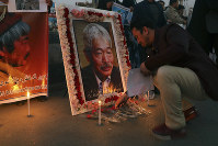 An Afghan man lights a candle in front of a portrait of Tetsu Nakamura, a Japanese physician engaged in aid work who was killed Dec. 4 in a shooting in eastern Afghanistan, during a vigil in Kabul, Afghanistan on Dec. 5, 2019. (AP Photo/Altaf Qadri)