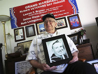 In this Nov. 17, 2016, file photo, Lauren Bruner, a survivor of the USS Arizona which was attacked on Dec. 7, 1941, holds with a 1940 photo of himself at his home in La Mirada, Calif. Divers will place the ashes of Bruner in the wreckage of his ship during a ceremony this weekend in Pearl Harbor, Hawaii. Bruner died earlier in 2019 at the age of 98. (AP Photo/Reed Saxon)