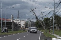 Vehicles pass by toppled electrical poles as Typhoon Kammuri slammed Legazpi city, Albay province, southeast of Manila, Philippines on Dec. 3, 2019. (AP Photo)