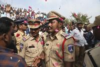 People throw flower petals on the Indian policemen guarding the area where rape accused were shot, in Shadnagar, India, 0n Dec. 6, 2019. (AP Photo/Mahesh Kumar A.)