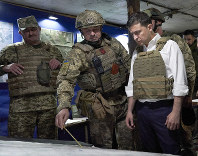 In this Oct. 14, 2019 file photo, Ukrainian President Volodymyr Zelenskiy, right, listens to a serviceman as he visits the war-hit Donetsk region, eastern Ukraine. (Ukrainian Presidential Press Office via AP)