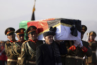 Afghan President Ashraf Ghani, foreground, and Afghan honor guards carry the coffin of Japanese physician Tetsu Nakamura during a ceremony before transporting his body to his homeland, at the Hamid Karzai International Airport in Kabul, Afghanistan, on Dec. 7, 2019. (AP Photo/Rahmat Gul)