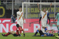 Inter Milan's Stefan de Vrij, right, on the ground after colliding with referee Gianpaolo Calvarese , left, on the ground during a Serie A soccer match between Inter Milan and Roma, at the San Siro stadium in Milan, Italy, on Dec.6, 2019. (AP Photo/Luca Bruno)