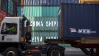 In this Thursday, July, 5, 2018 file photo, a jockey truck passes a stack of 40-foot China Shipping containers at the Port of Savannah in Savannah, Ga. (AP Photo/Stephen B. Morton)