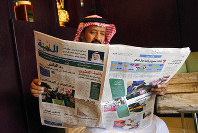 A man reads the daily Al-Madina newspaper fronted by a picture of Saudi King Salman at a coffee shop in Jiddah, Saudi Arabia, Saturday, Dec. 7, 2019. (AP Photo/Amr Nabil)