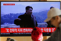 People watch a TV news program reporting North Korea's announcement with a file footage of North Korean leader Kim Jong Un, at the Seoul Railway Station in Seoul, South Korea, Sunday, Dec. 8, 2019. (AP Photo/Lee Jin-man)