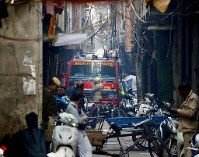 A fire engine stands by the site of a fire in a narrow lane in New Delhi, India, Sunday, Dec. 8, 2019. (AP Photo/Manish Swarup)