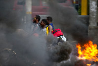 In this Sept. 17, 2019 file photo, a moto-taxi driver takes two passengers past a burning barricade during a protest against fuel shortages in Port-au-Prince, Haiti. Haiti's economy, already fragile when the new round of protests began in mid-Sept., is in deep trouble with spiraling inflation and dwindling supplies, including fuel. (AP Photo/Dieu Nalio Chery, File)