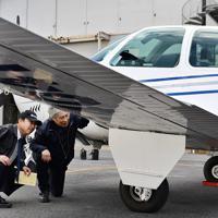 渋谷さんとともに訓練機を点検する植野廣園さん(左端)=大阪府八尾市の八尾空港で、猪飼健史撮影