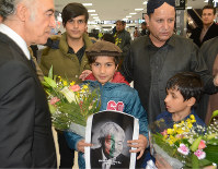 Afghan Ambassador to Japan Bashir Mohabbat, left, stands next to children holding bouquets and a photo of Japanese doctor Tetsu Nakamura, who was fatally shot in Afghanistan, as Afghan residents in Japan gathered at Narita International Airport in the city of Narita, Chiba Prefecture, on Dec. 8, 2019. (Mainichi/Tadakazu Nakamura)