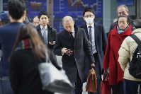 People walk by an electronic stock board of a securities firm in Tokyo, on Dec. 9, 2019. (AP Photo/Koji Sasahara)