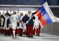 In this Feb. 7, 2014 file photo, Alexander Zubkov of Russia carries the national flag as he leads the team during the opening ceremony of the 2014 Winter Olympics in Sochi, Russia. (AP Photo/Mark Humphrey)