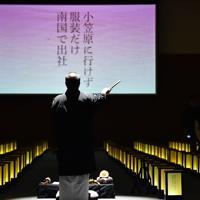 使われなかった年次有給休暇を供養するイベント「有給浄化」で、映し出されたエピソードを前に読経する僧侶の佐山拓郎さん=大阪市中央区で2019年12月10日午後7時35分、山崎一輝撮影