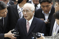In this June 14, 2005 file photo, Kim Woo-choong, center, former chairman of collapsed conglomerate Daewoo Group, answers reporters' questions as he arrived at the Supreme Prosecutor's Office in Seoul, South Korea. (AP Photo/ Lee Jin-man)