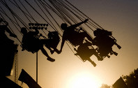 In this July 23, 2009 file photo, children are silhouetted by the setting sun as they ride a swing ride during the Canyon County Fair in Caldwell, Idaho. (Greg Kreller/The Idaho Press-Tribune via AP)
