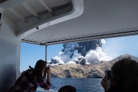 In this Dec. 9, 2019 photo provided by Michael Schade, tourists on a boat look at the eruption of the volcano on White Island, New Zealand. (Michael Schade via AP)