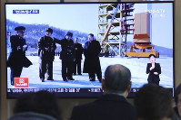 A man watches a TV screen showing a file image of the North Korean leader Kim Jong Un at his county long-range rocket launch site during a news program, at the Seoul Railway Station in Seoul, South Korea, on Dec. 9, 2019. (AP Photo/Ahn Young-joon)