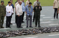 In this Dec. 13, 2018 file photo, Philippine President Rodrigo Duterte, center, looks at hundreds of guns and weapons confiscated during a pro-Islamic State group siege in Marawi, southern Philippines, at the Philippine Army Headquarters in Manila, Philippines. (AP Photo/Aaron Favila)
