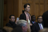 Myanmar's leader Aung San Suu Kyi enters the court room of the International Court of Justice for the first day of three days of hearings in The Hague, Netherlands, on Dec. 10, 2019. (AP Photo/Peter Dejong)