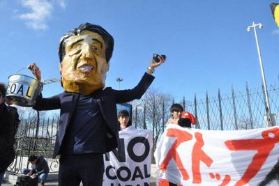 COP25会場前で横断幕などを掲げて日本政府に石炭火力発電廃止を求めるNGOメンバーら=スペイン・マドリードで5日、鈴木理之撮影