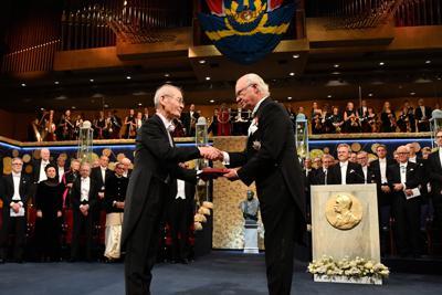 スウェーデンのカール16世グスタフ国王(右)からノーベル化学賞を授与される吉野彰・旭化成名誉フェロー=ストックホルムのコンサートホールで10日、AP