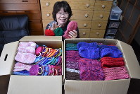 Keiko Minomo is seen smiling in front of boxes full of socks and crochet dishcloths she knitted in hopes to keep the victims of Typhoon Hagibis warm, in the city of Takanabe, Miyazaki Prefecture, on Dec. 4, 2019. (Mainichi/Yuka Shiotsuki)