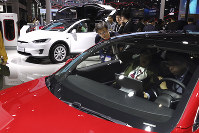 In this April 17, 2019, photo, attendees take a look at electric cars from Tesla at the Auto Shanghai 2019 show in Shanghai. (AP Photo/Ng Han Guan)