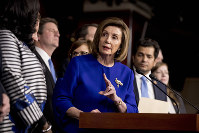 House Speaker Nancy Pelosi of Calif., accompanied by House Congress members, speaks at a news conference to discuss the United States Mexico Canada Agreement (USMCA) trade pact, on Dec. 10, 2019, on Capitol Hill in Washington. (AP Photo/Andrew Harnik)