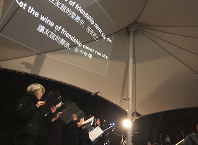 In this Dec. 10, 2019 photo, lyrics are projected on a canopy as a theater troupe performs Les Miserables at an outdoor event space in Hong Kong. (AP Photo/John Leicester)