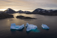 In this Aug. 16, 2019, file photo, large icebergs float away as the sun rises near Kulusuk, Greenland. (AP Photo/Felipe Dana)