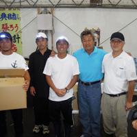 寄贈されたLED付き帽子をかぶり、梅宮辰夫さん(右から2人目)と記念撮影する田老地区の漁師たち=岩手県宮古市田老地区で2011年9月2日、吉村周平撮影