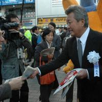 飲酒運転根絶キャンペーンで、通行人にチラシを配る梅宮辰夫さん(右)=東京都港区のJR新橋駅前で2010年12月1日、伊澤拓也撮影
