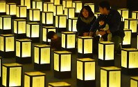 A family is seen among the rows of lanterns describing regrets over being denied paid leave, in Chuo Ward, Osaka, on Dec. 10, 2019. (Mainichi/Kazuki Yamazaki)